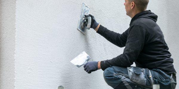 Mężczyzna nakłada dekoracyjny tynk elewacyjny na fasadę domu